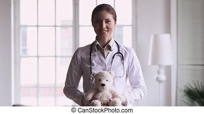 teddy, heureux, femme, regard, appareil photo, pédiatre, docteur, tenue, ours