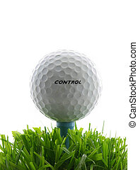 Golf ball on tee, in the grass. Word control written on ball