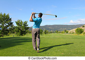 Young male golfer hitting a driver from the tee-box