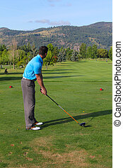 Young male golfer preparing for his tee-shot