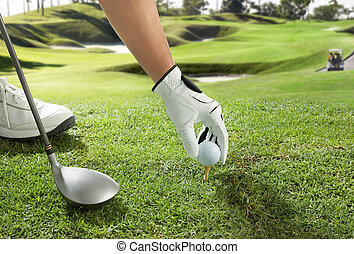 tee up - hand placing a golf ball on tee