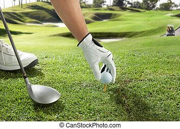 tee up - hand placing a golf ball on tee