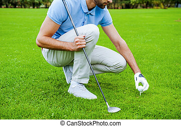 Teeing up. Close-up of golfer placing a golf ball on tee prior