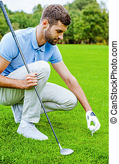 Teeing up. Confident young male golfer placing a golf ball on tee prior