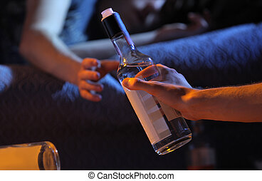 Teen alcohol addiction concept - Two young men get drunk at...
