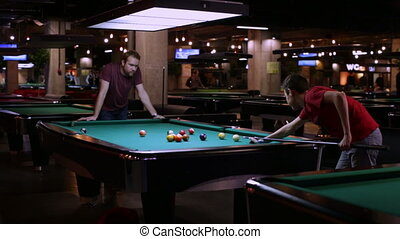 Teen and man playing in pocket billiards