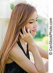 Teen Asian girl using cell phone. - Closeup portrait of a...