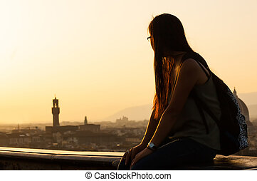 Teen at sunset watching the view of Florence.