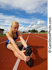 A Pretty teen stretching before a race at the track