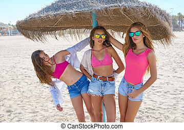 teen best friends girls under thatch umbrella having fun on...