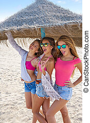 teen best friends girls under thatch umbrella