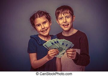 Teen boy and girl of seven are holding a lot of money and smiling