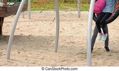 Teen boy and girl on swing