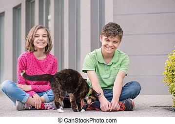 Teen siblings boy and girl cuddle with cat  Teen siblings
