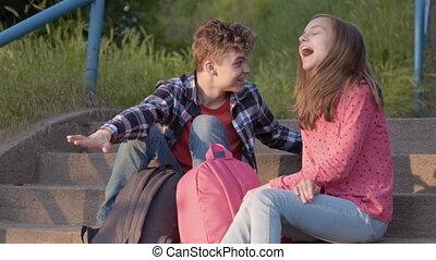 Teen boy and girl sitting on stairs - Happy teenage boy...