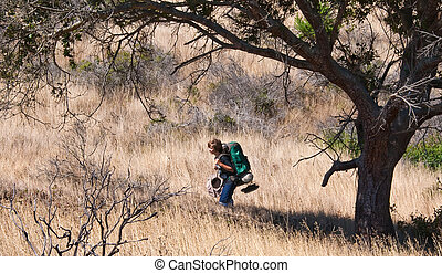 Teen hiking with full backpack through grasslands