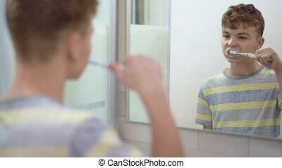 Teen boy brushing teeth - Morning in the bathroom. Teen boy...