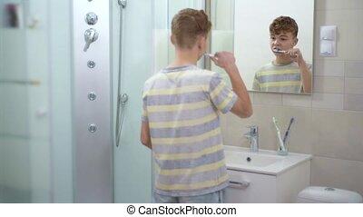 Teen boy brushing teeth