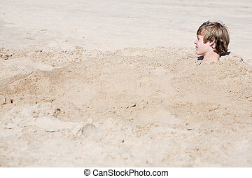 Teen boy buried in the sand