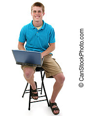 Teen Boy Computer - Cute freckled male teen sitting on stool...