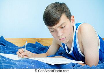 Teen boy doing homework on his bed
