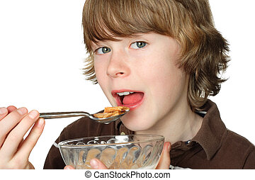 A teen boy ready to eat a spoonful of cereal