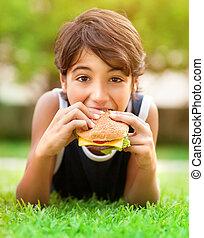 Teen boy eating burger outdoors