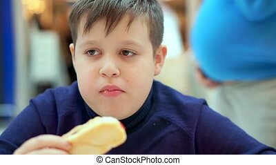 Teen boy eating hot dog in fast food cafe