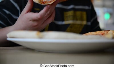 Teen boy eating pizza in cafe