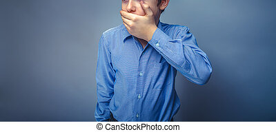 Teen boy European appearance brown hair hand closed mouth...