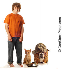 teen boy feeding his dog and cat