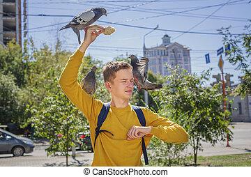 Teen boy feeds pigeons on city street
