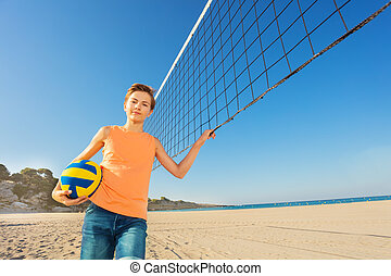 Teen boy getting ready for beach volleyball game
