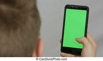 Teen boy holds in hand a black smartphone with a green...