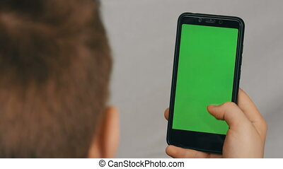 Teen boy holds in hand a black smartphone with a green screen on white background. Technology