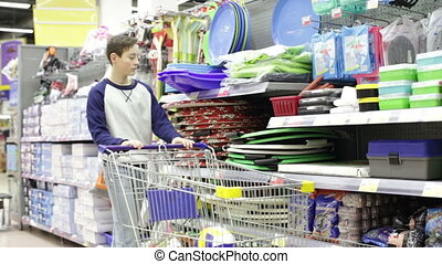 Teen boy in the store takes a sledge with handles
