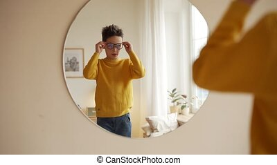 teen boy is choosing new eyeglasses in front of a mirror.