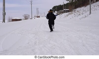 Teen boy is running on the road covered with snow. Active holidays for children in winter park. A cloudy winter day
