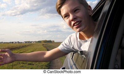 Teen boy looks out the car window and waves. The car is moving on a country road