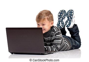 Teen boy lying on floor with laptop