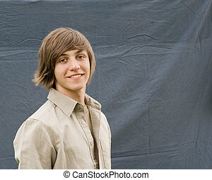 Outdoor spring portrait of a teenaged boy with a backdrop.