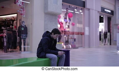 Teen boy playing phone sitting on the bench