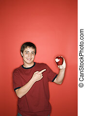 Teen boy pointing to apple.