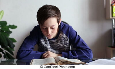 Teen boy reading a book at the table in home