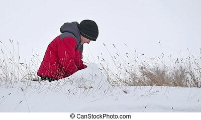 Teen boy rolling a ball of snow to build a fortress. sculpts winter snowman snow
