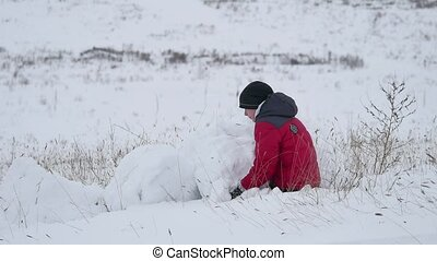 Teen boy rolling a ball of snow winter to build a fortress. sculpts snowman snow