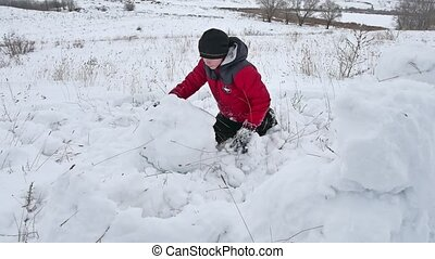 Teen boy rolling a ball of winter snow to build a fortress. sculpts snowman snow