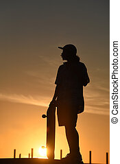 Teen boy silhouette with skateboard on summer day