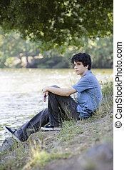 Teen Boy Sitting By Lake