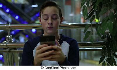 Teen boy sitting near tree and playing smartphone